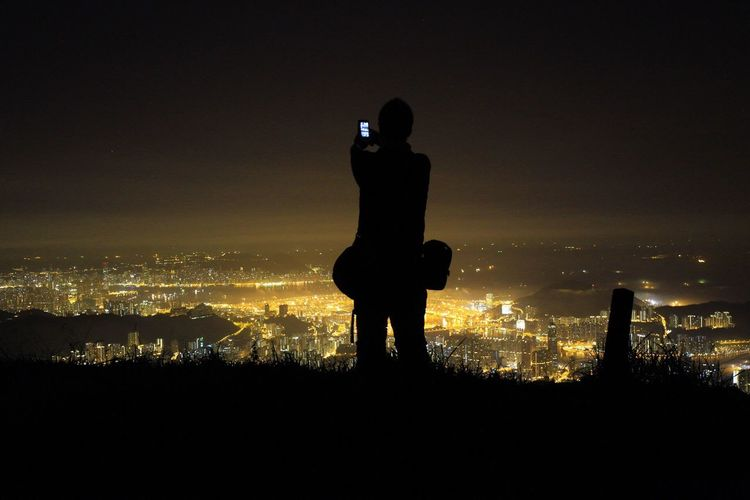 Person photographing illuminated cityscape at night