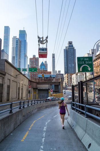 A female jogging under the Roosevelt Island Tram in New York City. Cityscape Commuting Females NYC Skyscrapers Tram Architecture Bridge - Man Made Structure Built Structure Cityscape Day Jogger Jogging Outdoors Real People Rear View Runner Skyscraper Transportation Urban Women