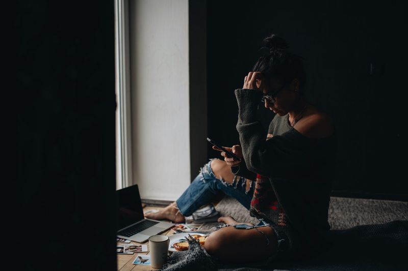 Woman using mobile phone while siting at home