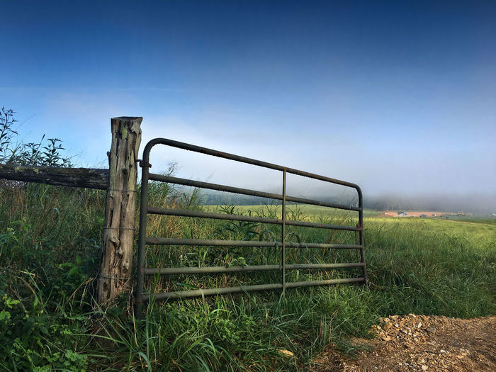 Old gate on field against sky