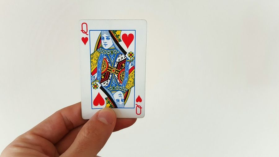 Cropped Image Of Hand Holding Queen Of Hearts Against White Wall
