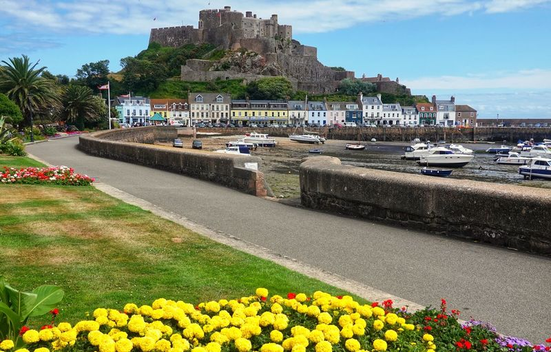 Gorey castle Gorey Castle Jersey Channel Island UK Architecture Beauty In Nature Built Structure City Cloud - Sky Flower Flowerbed Flowering Plant Freshness Gorey Growth Jeresy Nature Plant Sky Travel Destinations Water