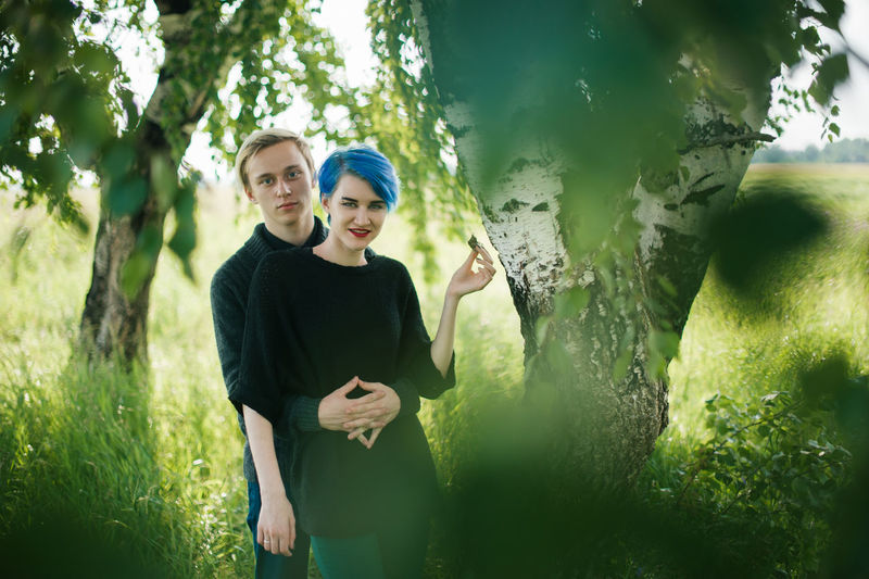 Portrait of young man and woman embracing by tree on field