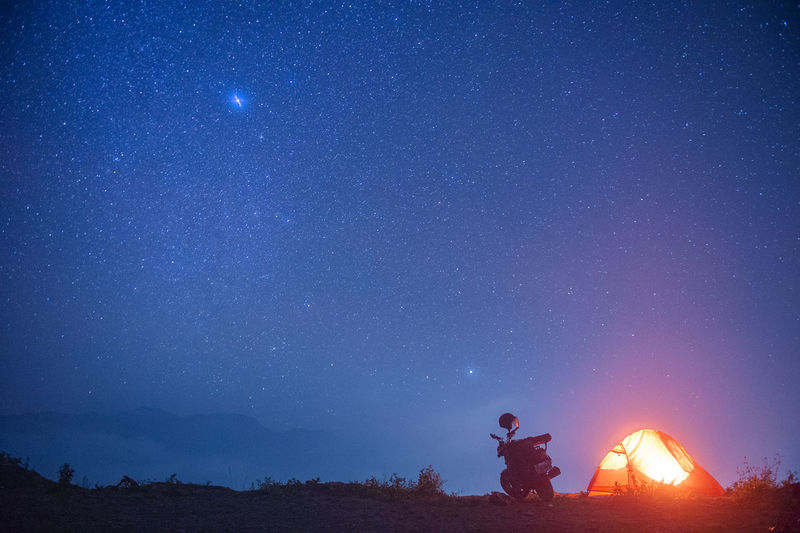 Low angle view of man standing against star field at night
