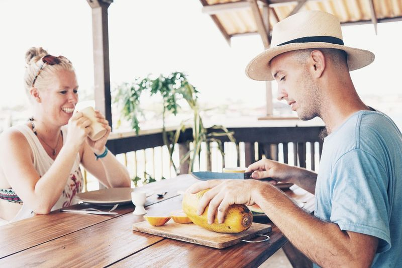Man cutting fruit while sitting with female friend on table