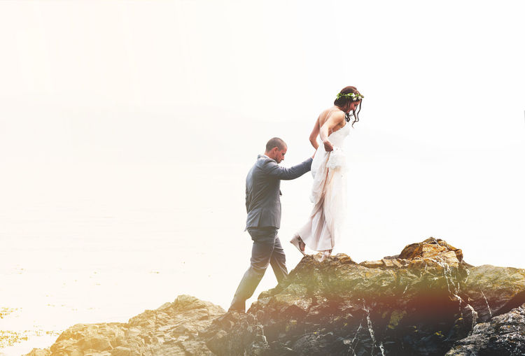 Wedding Portrait Romantic Romance Love Holding Hands Wedding Wedding Photography Wedding Dress Wedding Day Rocky Coastline Rocky Beach Leading The Way Leading Bridegroom Well-dressed Full Length Men Beach Standing Bride Challenge Suit Shore Calm Photographer Groom Horizon Over Water Human Connection