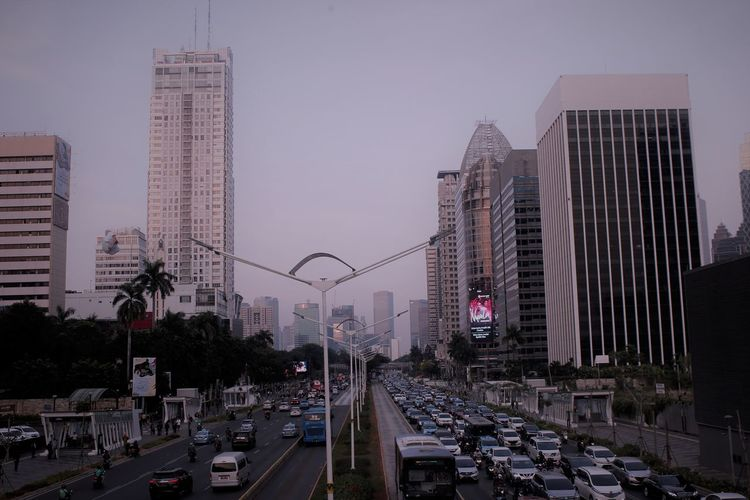 Vehicles on road amidst buildings against sky in city
