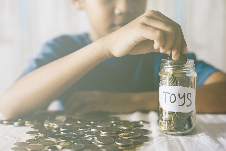 Midsection Of Boy Putting Coins In Jar On Table