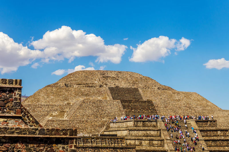 Tourists at pyramid of the sun against blue sky