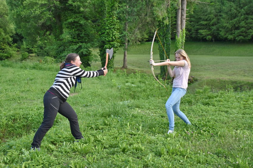Ax Bow And Arrow Casual Clothing Emotion Friendship Full Length Fun Grass Leisure Activity Nature Outdoors People Plant Standing Togetherness Tree Two People Women