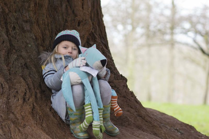 Portrait Of Cute Girl Holding Toy While Sitting By Tree Trunk During Winter