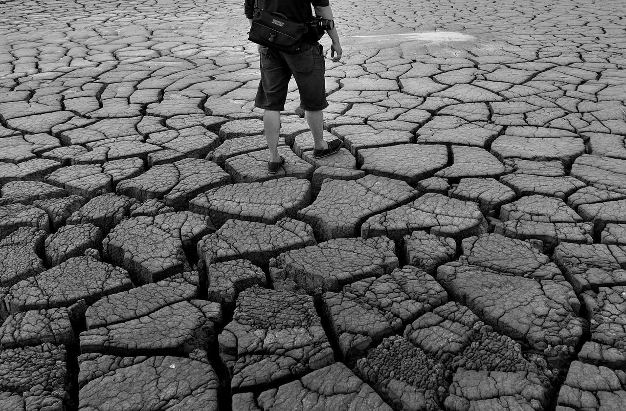 Low section of man standing on drought land