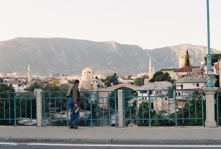 A fisherman overlooking the river and Mostar Bridge in Bosnia. - Photos taken on 35mm film with Canon AE-1 Program analog camera. Streetwise Photography Streetphotography Street Analogue Photography Analog 35mm Film Film Photography Canon AE-1 Canon Canon AE-1 Program  Architecture Built Structure Fujifilm FujicolorC200 The Week on EyeEm Best Of EyeEm My Best Photo Mostar Bosnia And Herzegovina Lifestyles The Art Of Street Photography