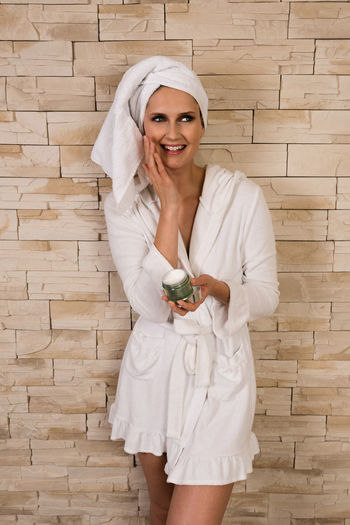 Happy woman in bathrobe holding face cream against wall