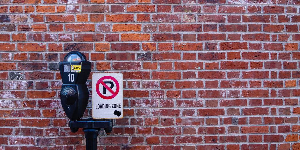 Loading here Brick Wall Brick Wall Wall - Building Feature Communication Sign Text Red Architecture Day Information Warning Sign Information Sign Close-up Message Outdoors Capital Letter Parking Parking Sign Parking Meter Coin Pay Color Colorful Loading