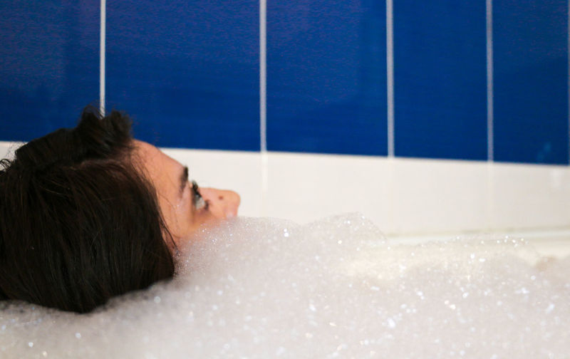 Close-up of woman relaxing in bathroom