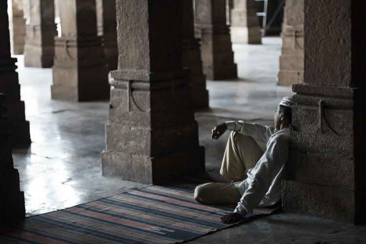 Muslim Man Leaning Against Column In Monument
