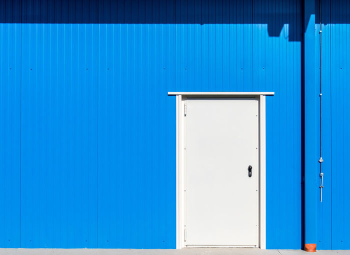 Exterior Of Blue Warehouse With Closed Door During Sunny Day