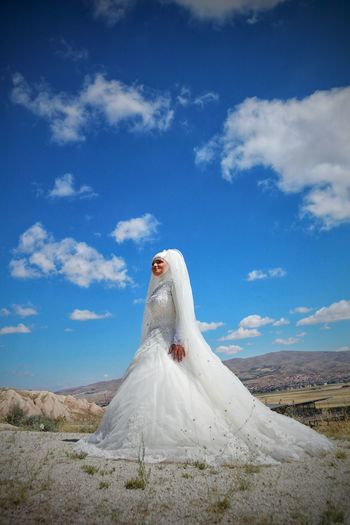 Smiling bride standing on field against blue sky