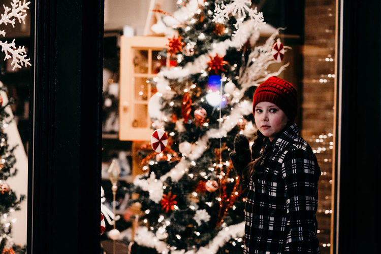 Christmas christmas tree Celebration Tree Decoration Winter Holiday Portrait Waist Up Christmas Decoration Indoors  Adult One Person Young Adult Women Emotion Window Looking At Camera Warm Clothing Christmas Ornament Christmas Lights Childhood Girl