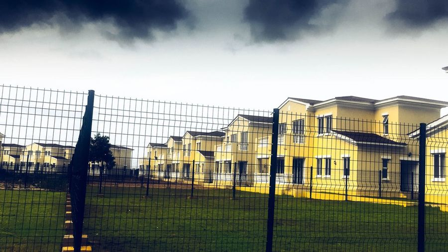 Black Clouds ☁️🌚 Town Apartment Green Green Color Gray Sky Yellow Dramatic Angles Dramatic Sky Housing Clouds And Sky Cloud - Sky Sky Fence Barrier Boundary Built Structure Cloud - Sky Architecture Safety Building Exterior Building Grass Protection Outdoors Security Nature