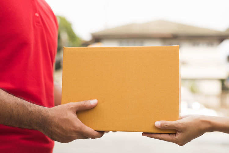 Close-up of man holding red box