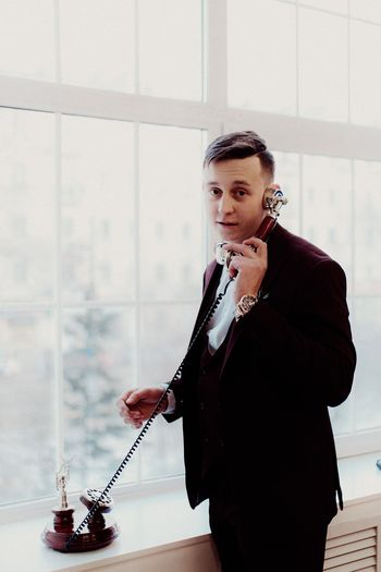 Portrait of man talking over telephone against window