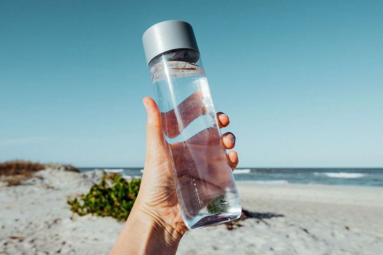 Female hand holding water bottle outdoor on sea shore health care concept for water balance.