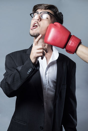Hand Punching Businessman Against Gray Background
