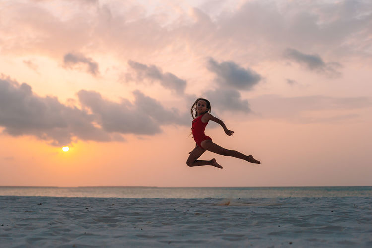 Man jumping over sea against sky during sunset