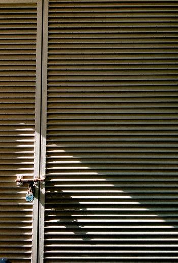 Full length of man walking on closed shutter