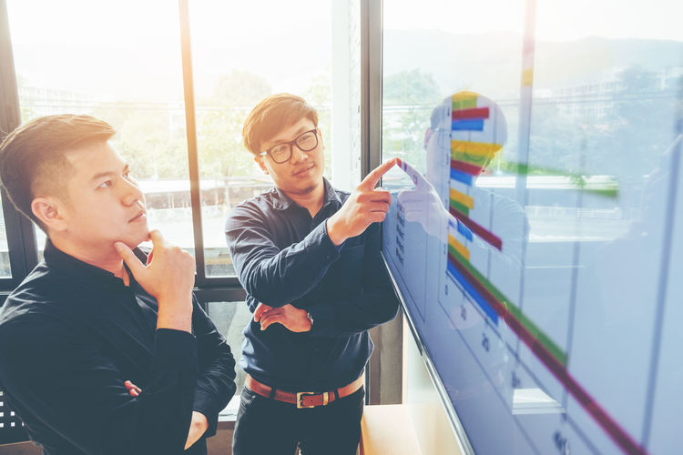 Businessman showing graph to colleague in office