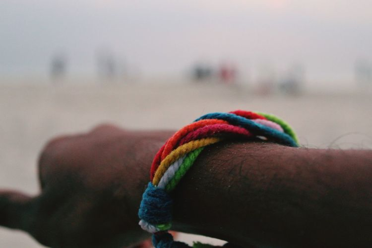 Close-up of human hand with multi colored band against the sky