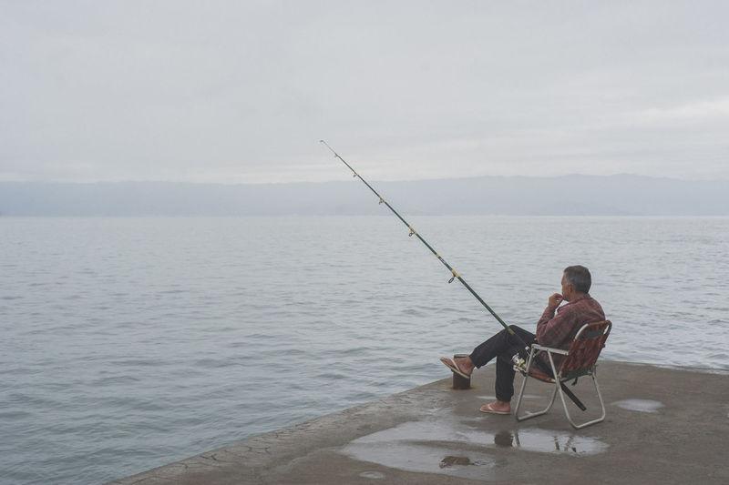 Silhouette of man fishing in lake