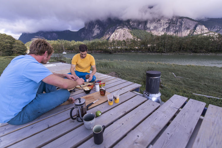 Rear view of men sitting by lake against mountains