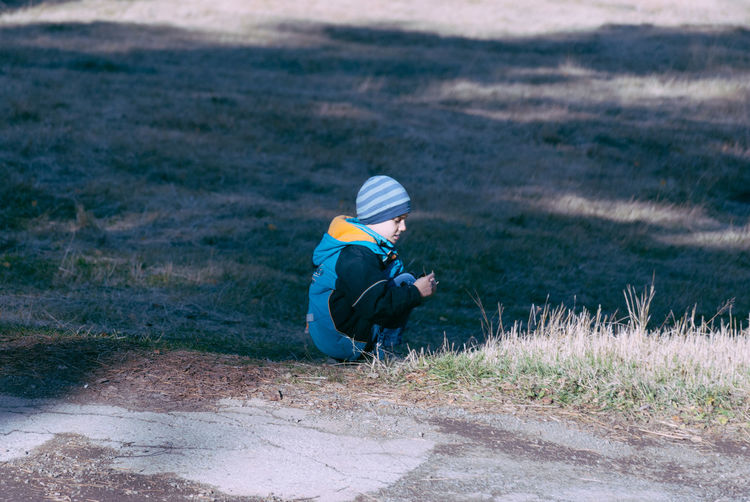 Boy wearing warm clothing while crouching on field