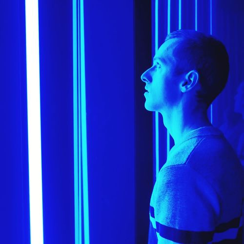 Side view of young man standing by illuminated wall