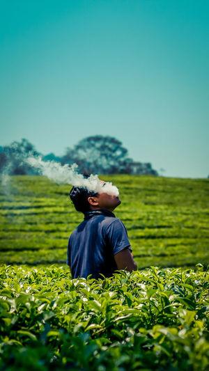 Man emitting smoke while standing amidst plants
