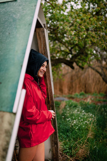 Smiling girl wearing red raincoat takes shelter from the rain Raincoat Red Raining Girl Young Woman Attractive Field One Person Only Millennial Pink Brunette Braid Cold Temperature Gooseflesh Goose Pimples Smiling Hairstyle Outdoors Green Color Focus On Foreground Day Holding Land Young Women Nature Young Adult Women Standing Casual Clothing Lifestyles Leisure Activity Tree Three Quarter Length Plant One Person Real People Hood Bare Legs Cloudy Day
