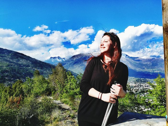 Smiling woman holding hiking poles while standing on mountain against sky
