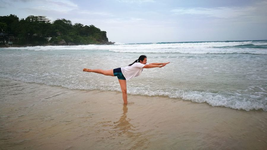 Woman Standing On One Leg At Sea Shore