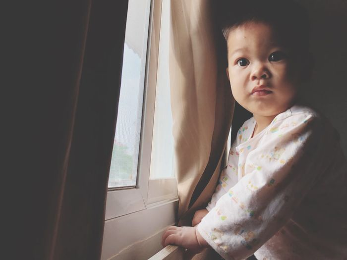 Boy standing by the window Window One Person Child Indoors  Real People Home Interior Childhood Lifestyles Cute Day Babyhood Looking Toddler  Portrait Innocence Standing Looking At Camera Contemplation