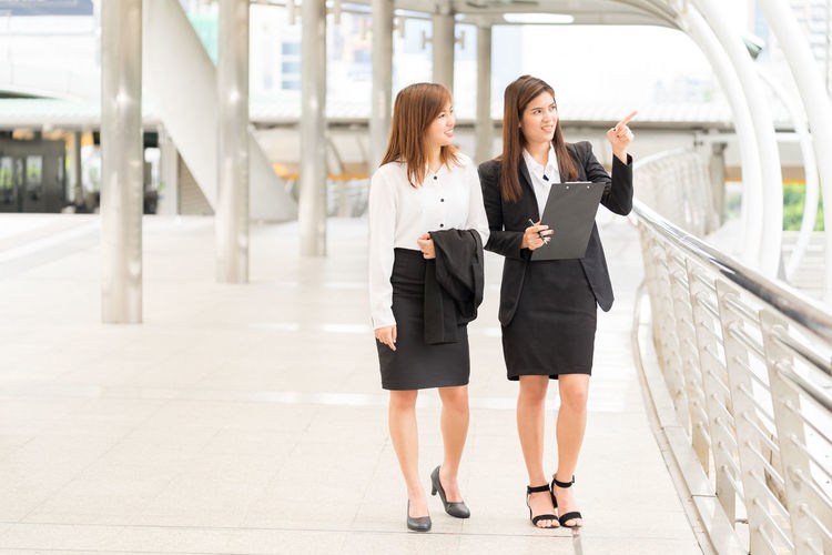 Businesswoman pointing while talking with female colleague by railing on footbridge
