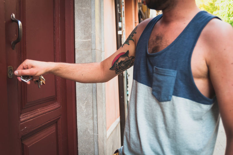 Midsection of man opening door with keys