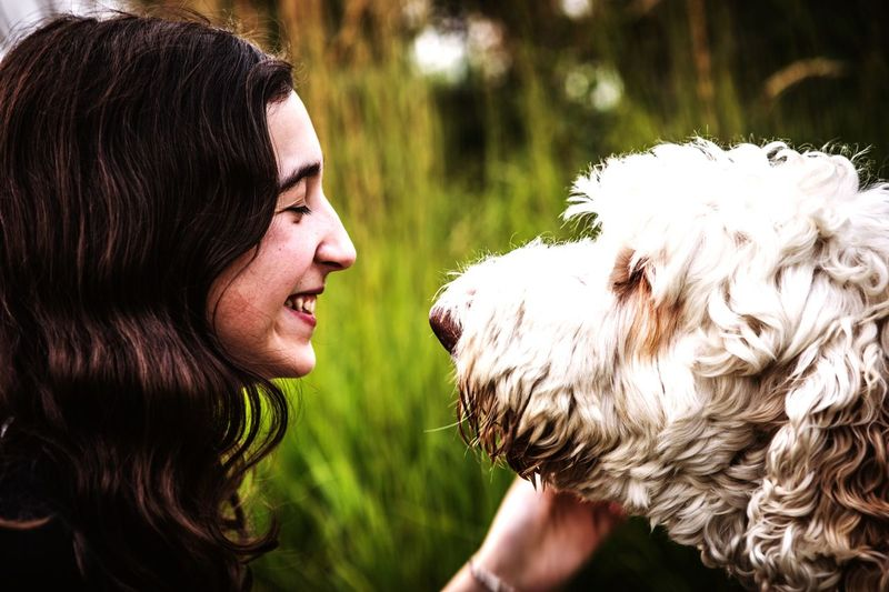 Side view of teenage girl with dog in park