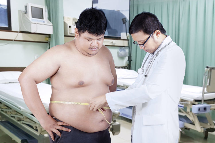 Doctor measuring shirtless male patient waist in hospital