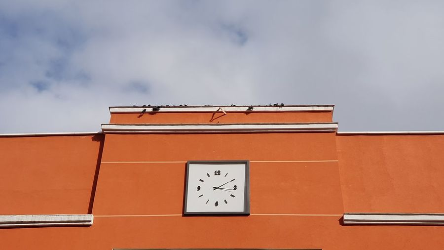 Low angle view of orange building against sky