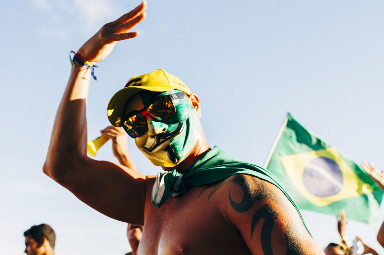 Low angle view of shirtless man with brazilian flag face paint against sky