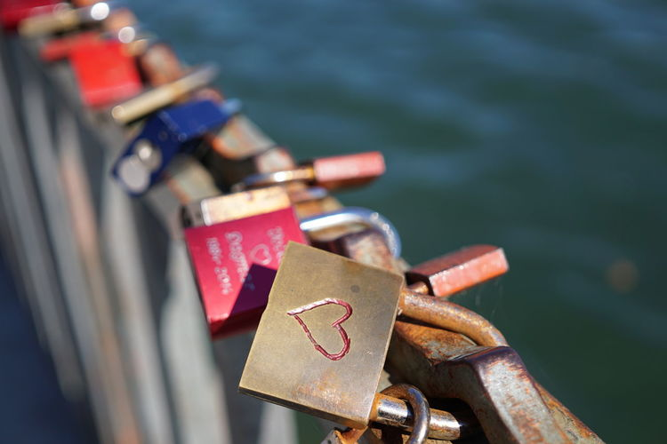 Close-Up Of Love Locks On Bridge Over River