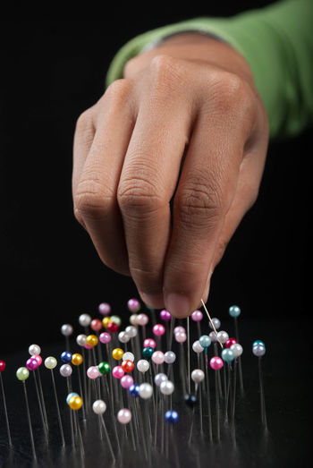 Cropped hand of person with colorful straight pins against black background